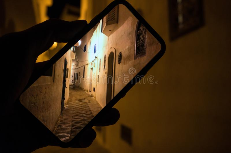 Closely image of hand holding mobile phone with photo of the night street in Asilah Medina, Morocco Atlantic Coast. Low stock photos