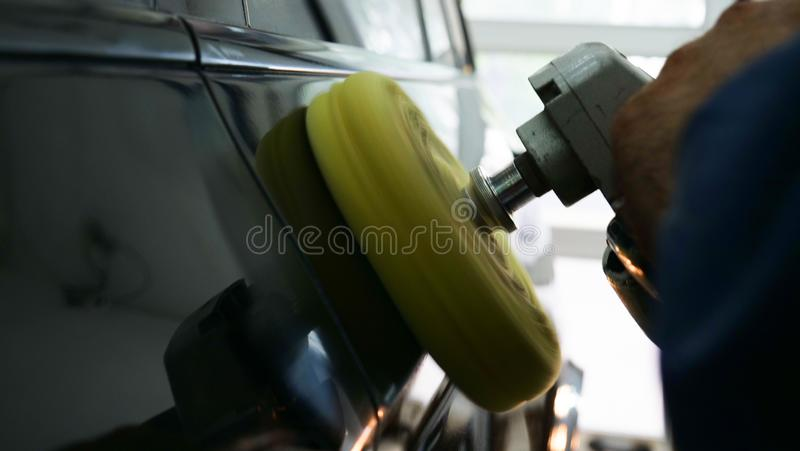 Closely shown as a professional worker polishes the transport car body using a polishing tool machine. Concept from: Auto serv. Ice, Car Painting, Machine royalty free stock images