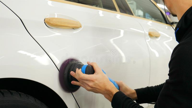 Closely shown as a professional worker polishes the transport car body using a polishing tool machine. Concept from: Auto serv. Ice, Car Painting, Machine royalty free stock photos