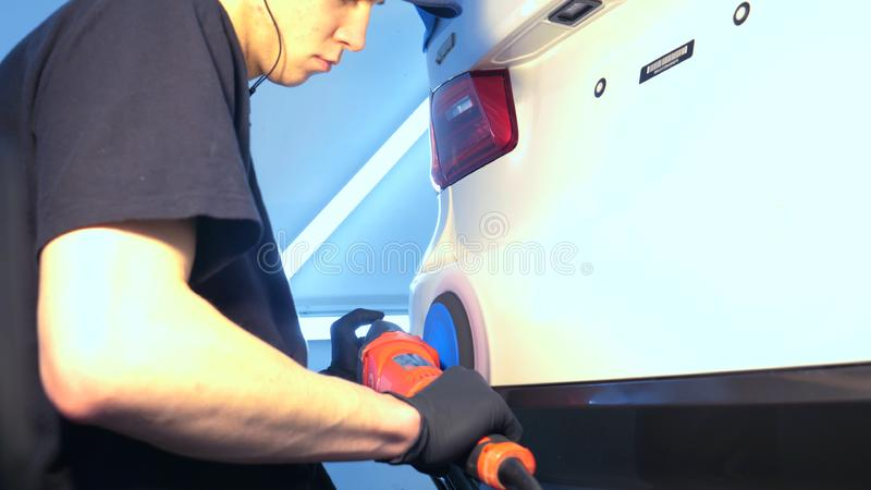 Closely shown as a professional worker polishes the transport car body using a polishing tool machine. Concept from: Auto serv. Ice, Car Painting, Machine stock photo