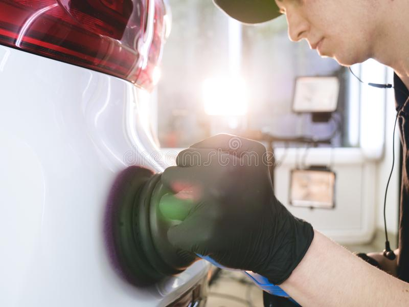 Closely shown as a professional worker polishes the transport car body using a polishing tool machine. Concept from: Auto serv. Ice, Car Painting, Machine stock photography