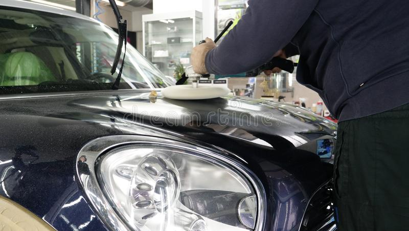 Closely shown as a professional worker polishes the transport car body using a polishing tool machine. Concept from: Auto serv royalty free stock image