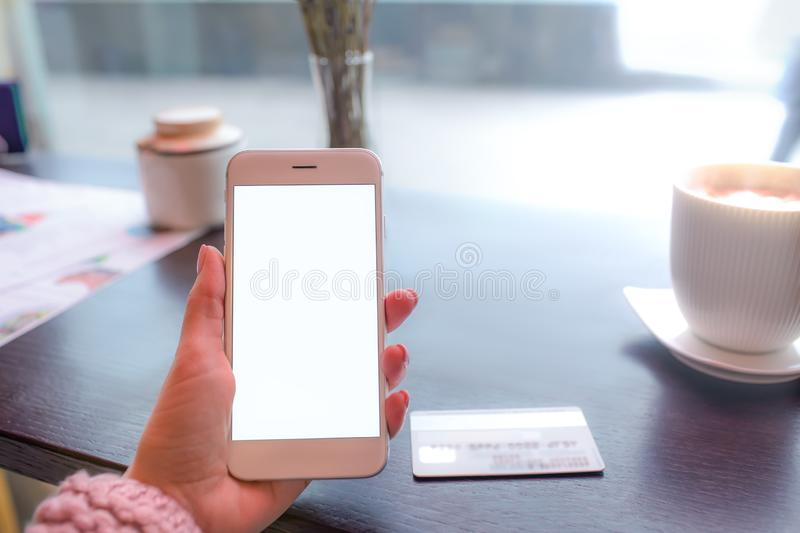 Closely woman lifestyle blogger holding smartphone with white empty mock up on the screen. Background for promotional content during online payment and using royalty free stock photography