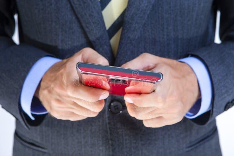 Closep de equipa as mãos com telefone celular vermelho fotografia de stock