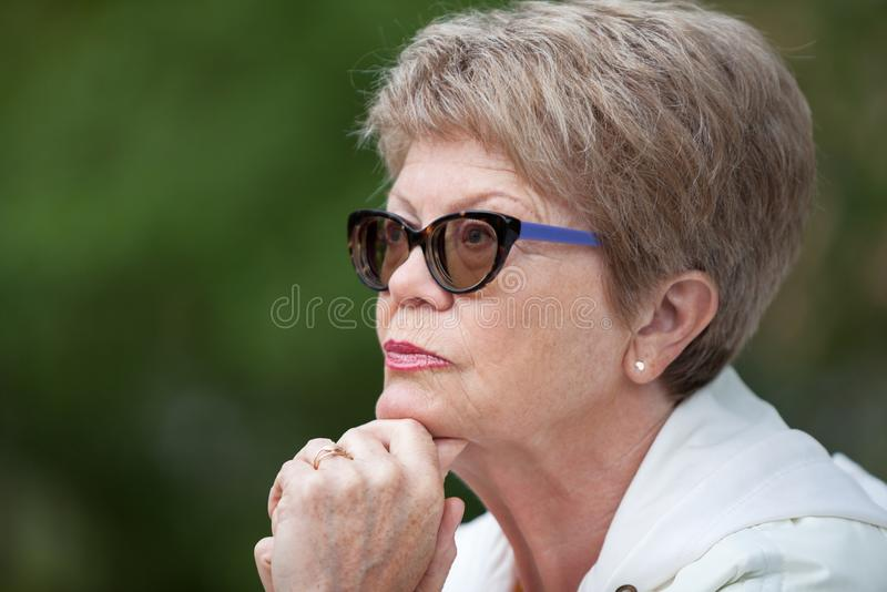 Closes up side view portrait of an elderly woman in glasses thinking with hand under head royalty free stock photography