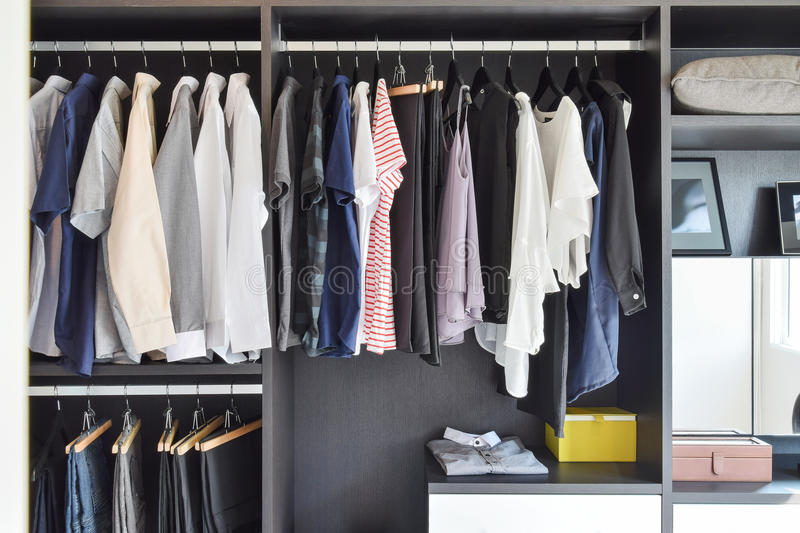 Closet with row of cloths hanging in black wardrobe stock images