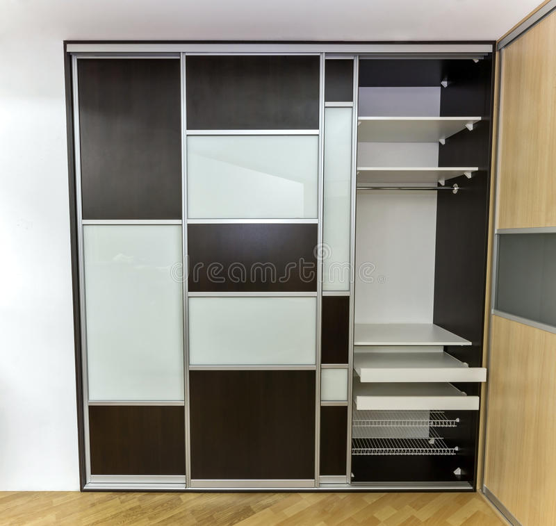 Closet with sliding doors. Modern closet with three sliding doors, made of laminated glass and plywood. One door is open in order to show interior of the closet stock image