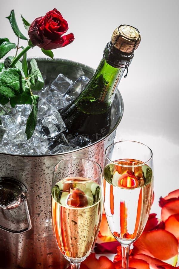 Closeu de la rosa del rojo y del champán frío para el día de tarjeta del día de San Valentín foto de archivo