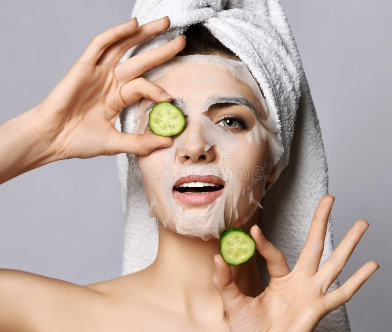 closeup Милая женщина с волосами в полотенце, косметическая moisturizing маска ткани на стороне держит куски огурца перл макроса  стоковые изображения rf