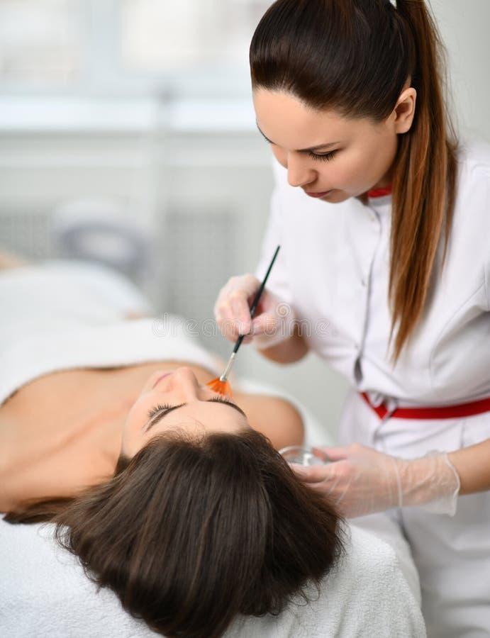 closeup Το Cosmetician προετοιμάζει τον ασθενή για μια καλλυντική διαδικασία Εφαρμόζει ήπια μια σύνθεση με μια βούρτσα στοκ φωτογραφία