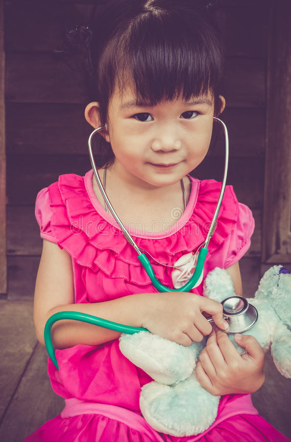 Closeup adorable asian girl playing doctor or nurse with plush t royalty free stock images