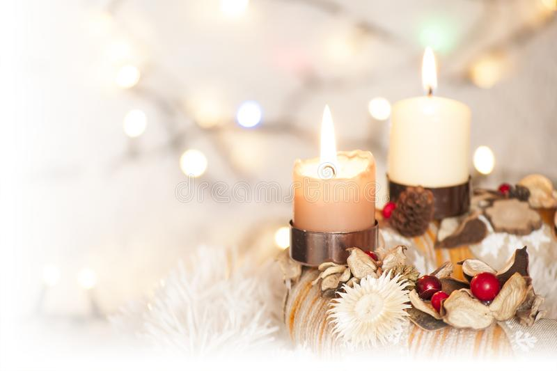 Closeup of Advent wreath with two burning candle and Christmas lights in background. Colorful closeup of Advent wreath with two burning candle and white blurry stock photo