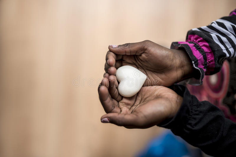 Closeup of African-American girl holding a marble made heart shape in her hands royalty free stock photos