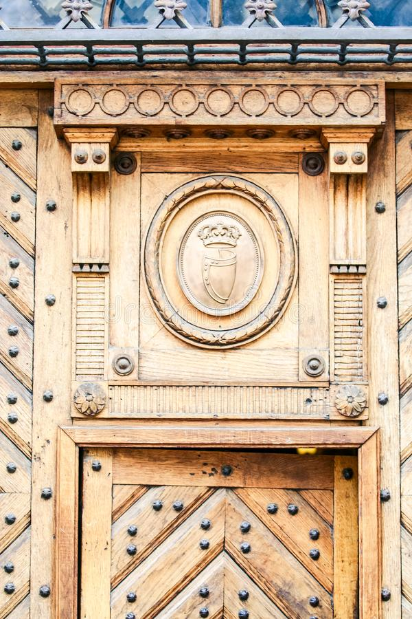 Age-old Brown Wooden Fretwork Door Metal Decor. Closeup age-old light brown wooden fretwork door with metal decoration royalty free stock image