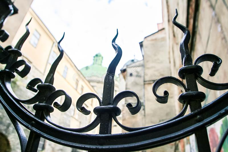 Closeup Age-old Metal Lace Gate against Old Houses. In european city Lviv stock photos