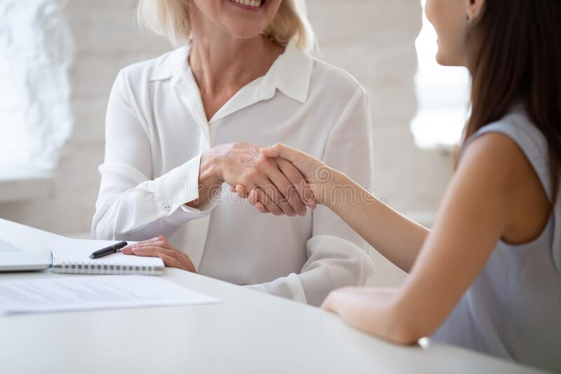 Closeup aged boss and millennial applicant handshaking starting job interview stock photography
