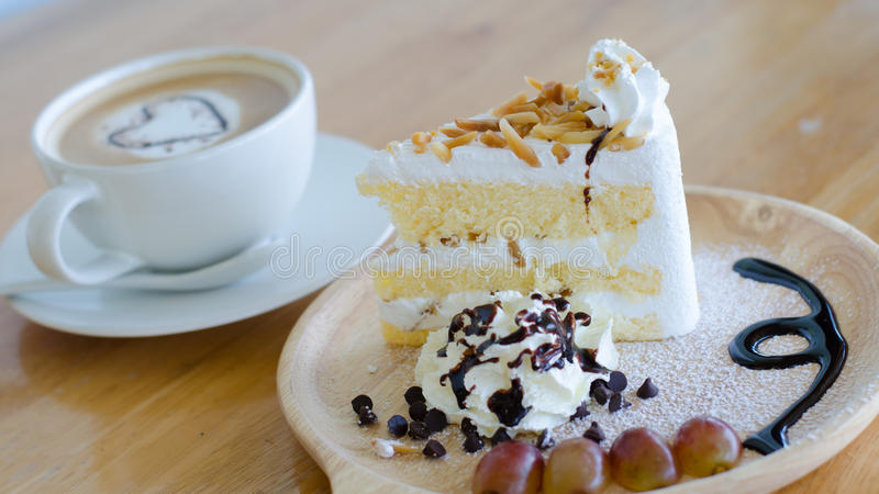 Closeup almond cake and coffee cup. With heart shape latte art on wood table royalty free stock photography