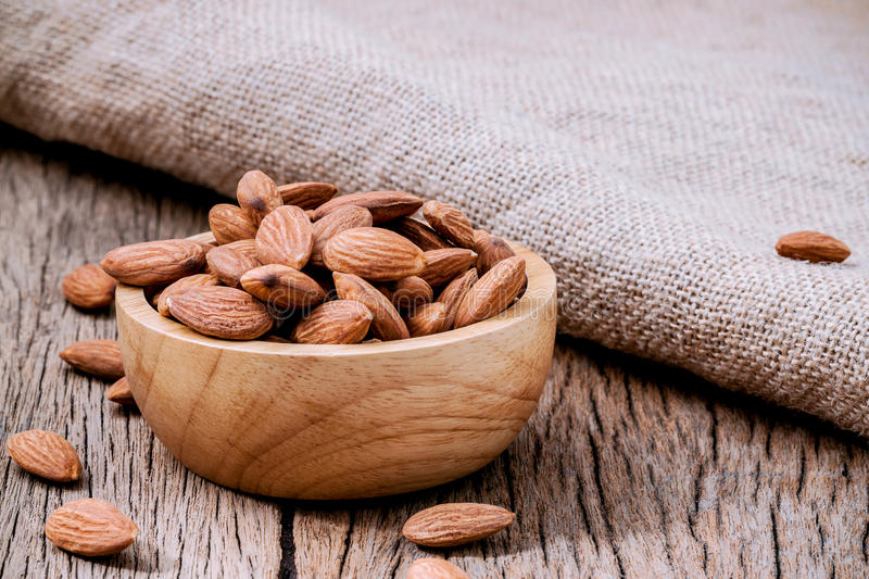 Closeup almonds kernels in wooden bowl with hemp sack on rustic stock photo