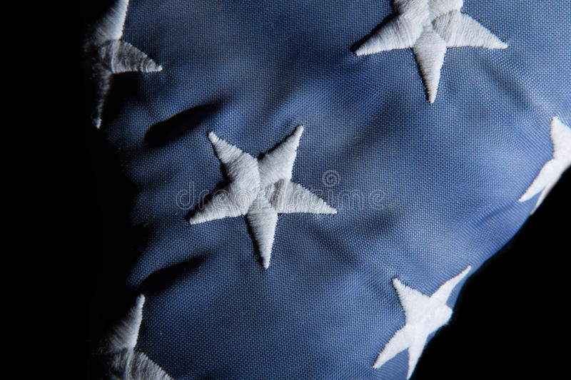 Closeup of an american flag. Close up of a used american flag on black stock image