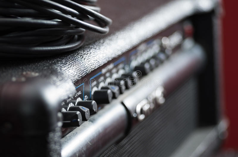 Closeup amplifier with row of buttons and knobs, descriptions turning blurry, cable bundle placed on top, studio. Equipment concept royalty free stock photography