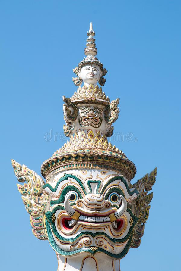 Closeup Ancient Head and face of Thai big giant statue with blue sky, Royal Grand Palace Wat pha kaew with blue sky, Bangkok in stock image