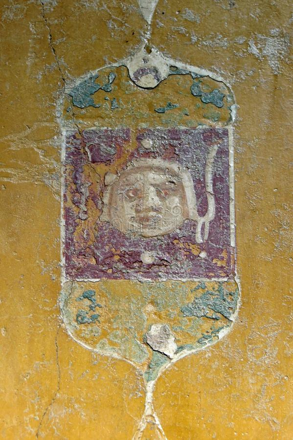 Closeup of an ancient tablinum showing a face in a frame on yellow background; Casa di Marco Lucrezio Frontone, Pompeii, Italy. The ancient Roman city Pompeii stock photography
