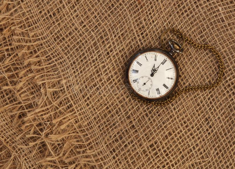 Closeup of old watch on old grungy sackcloth. Time passing concept stock photography