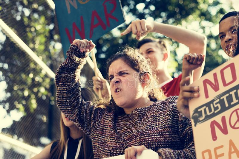 Closeup of angry teen girl protesting demonstration holding post. Ers antiwar justice peace concept stock images