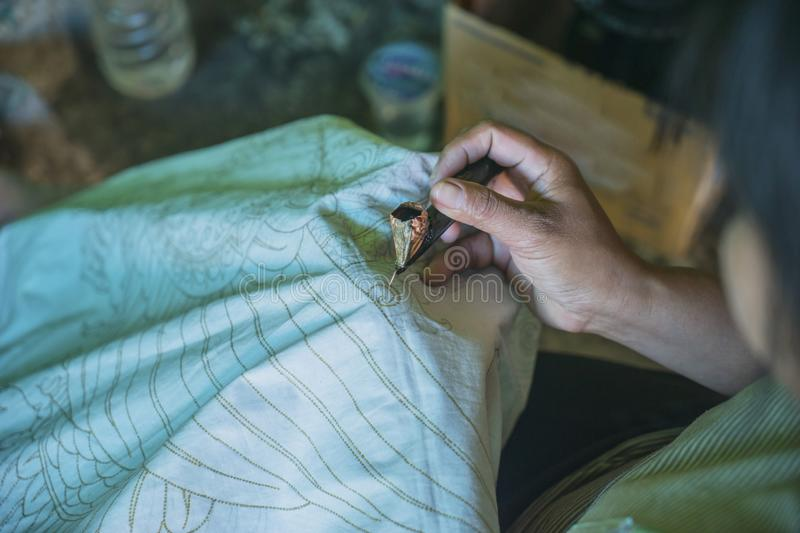 Anonymous woman using a canting. Closeup of anonymous woman making batik on a fabric while using a canting and wax stock photo