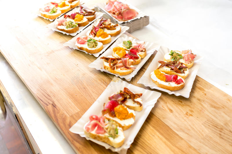 Closeup of antipasti and set of bruschetta lying on wooden board royalty free stock image