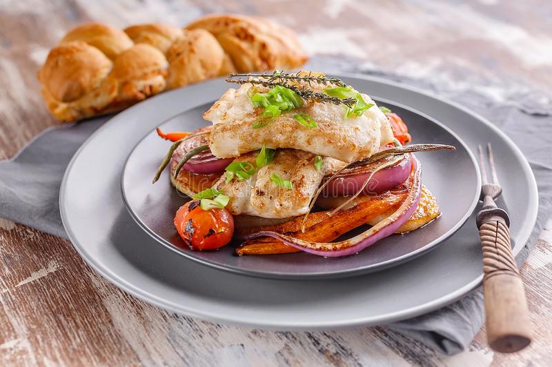 Closeup appetizing cod filet with red onion and herbs, baked potatoes and carrots on a side dish in a gray plate on a napkin. Tasty and healthy seafood royalty free stock photos