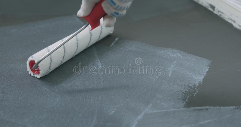 Closeup applying protective coating on the concrete floor royalty free stock photography