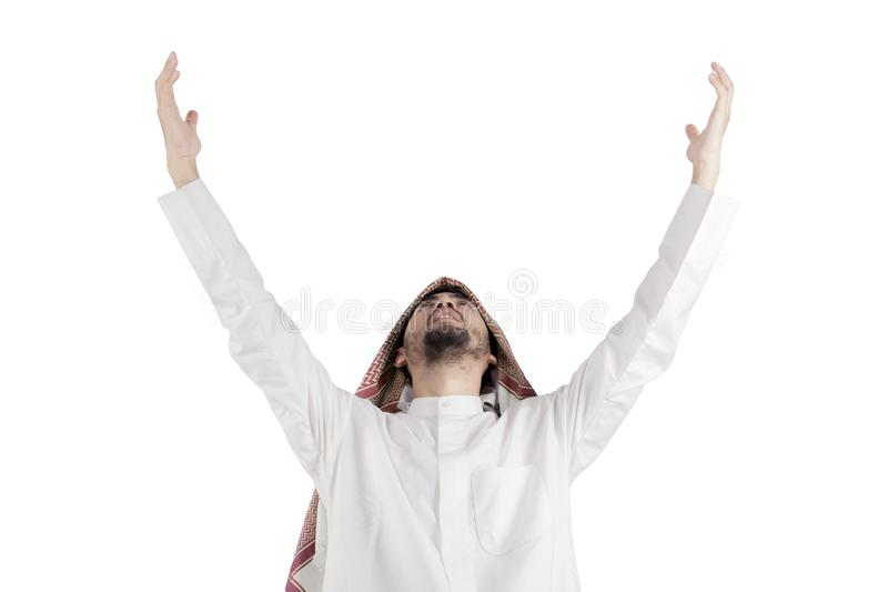 Arabian man praying to GOD. Closeup of Arabian man lifting his hands while praying to GOD, isolated on white background royalty free stock photography