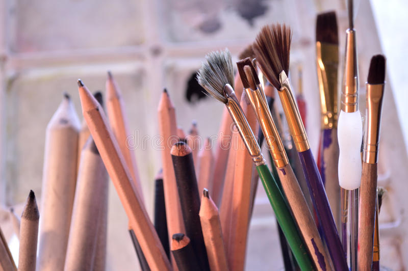 Closeup of art supplies in front of art palette. Painting,drawing and sketching tools. Graphite and charcoal pencils for fine art in the middle and blending royalty free stock images