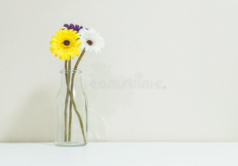 Closeup artificial colorful flower on transparent glass bottle on blurred white wood desk and cream color wallpaper at the wall. Room texture background royalty free stock photography