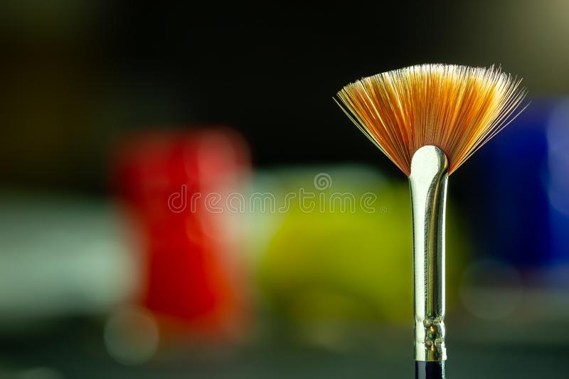 Artist paint brush and poster color bottle blur background. Closeup artist paint brush and poster color bottle blur background. Copy space for text. Concept of stock image