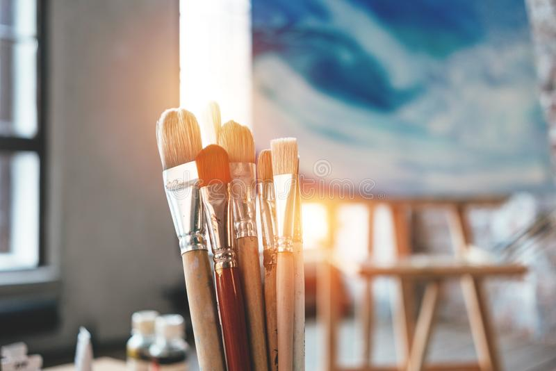 Closeup of artist paintbrushes and studio interior. Blurred background. Workshop or art class. Creative concept. Flare effect stock image