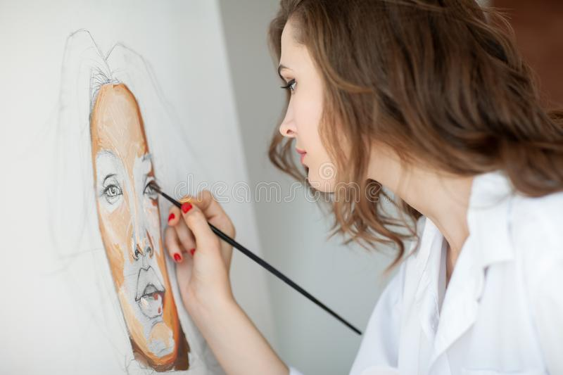 Closeup of artist painting woman portrait stock photography