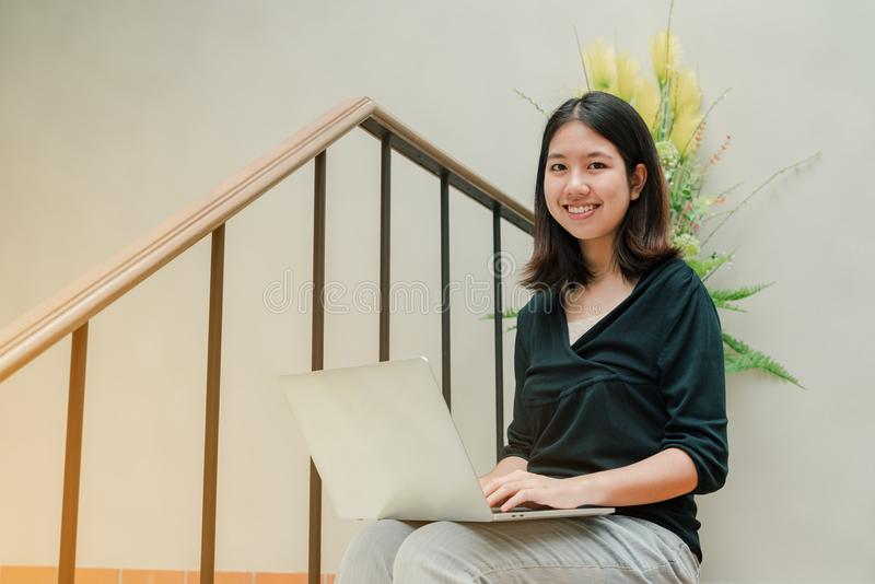 Closeup Asian beautiful woman Wearing a black shirt Sitting in the stairs in the house Use a laptop computer to work happily.  royalty free stock image