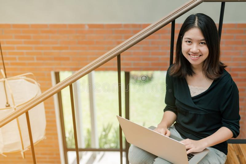 Closeup Asian beautiful woman Wearing a black shirt Sitting in the stairs in the house Use a laptop computer to work happily.  stock photo