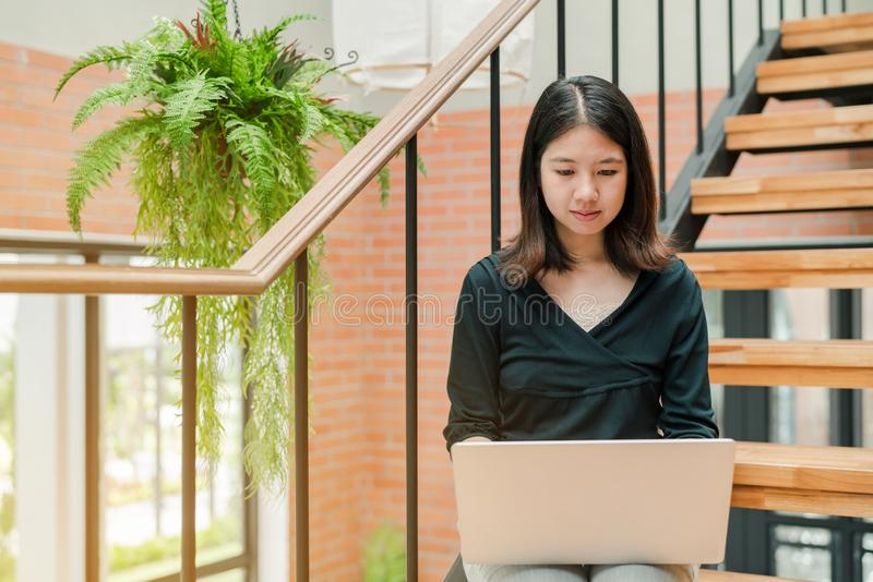 Closeup Asian beautiful woman Wearing a black shirt Sitting in the stairs in the house Use a laptop computer to work happily.  royalty free stock images
