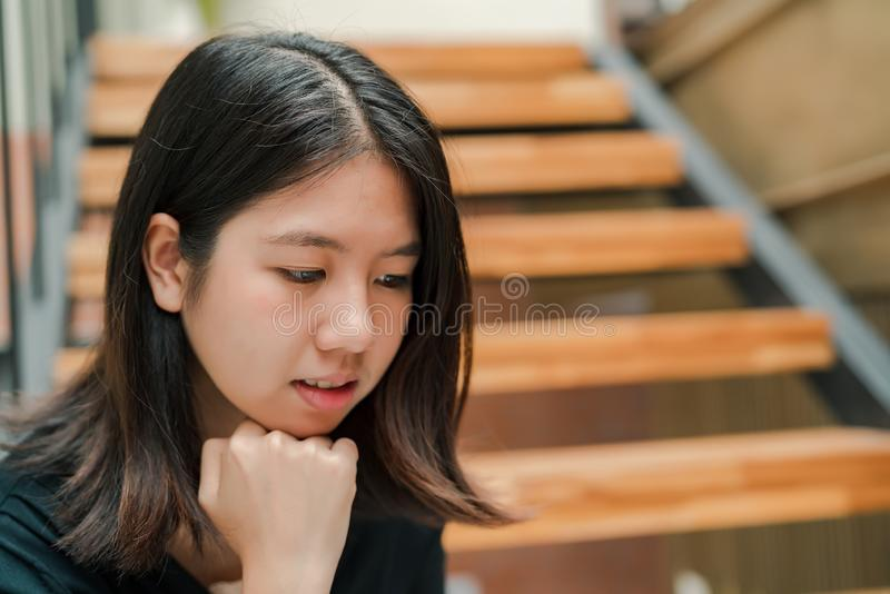 Closeup Asian beautiful woman Wearing a black shirt Sitting in the stairs in the house Use a laptop computer to work happily.  stock photography
