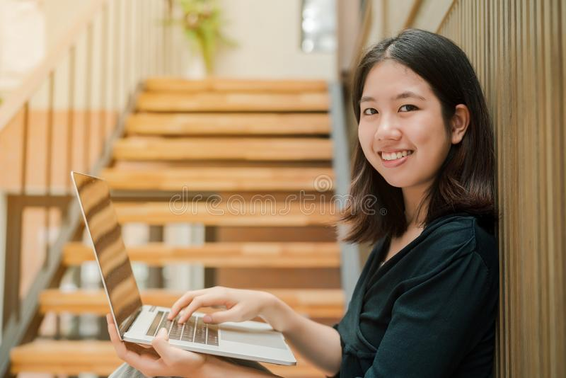 Closeup Asian beautiful woman Wearing a black shirt Sitting in the stairs in the house Use a laptop computer to work happily.  royalty free stock photo