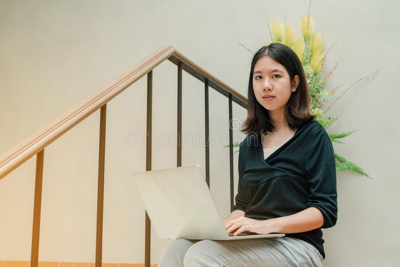Closeup Asian beautiful woman Wearing a black shirt Sitting in the stairs in the house Use a laptop computer to work happily.  royalty free stock photos