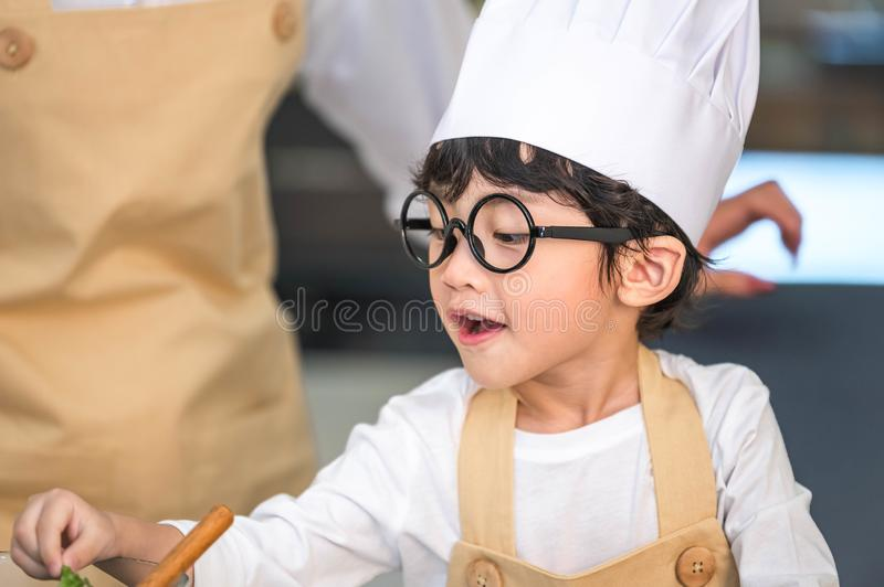 Closeup of Asian cute little boy wearing chef hat and apron with mother in home kitchen. Thai people and lifestyles concept. Job stock photo