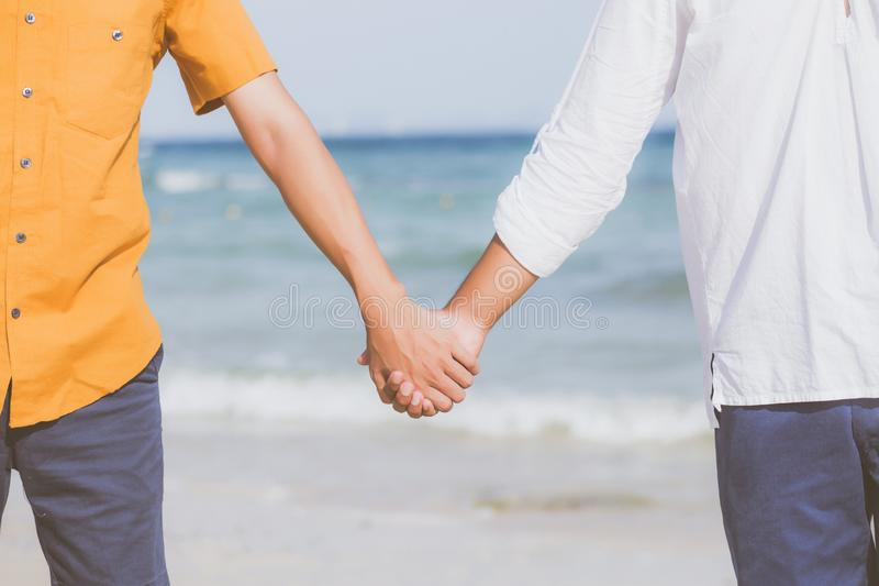 Closeup asian gay couple holding hands together on the beach with relax and leisure in summer stock photo