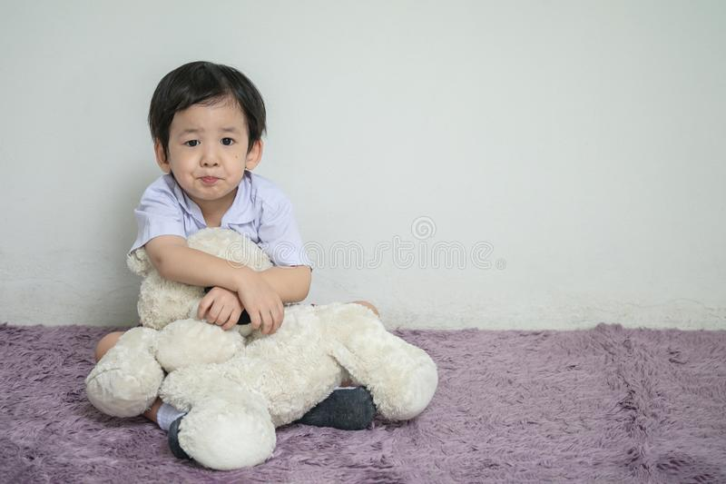 Closeup asian kid with boring face with bear doll sit on carpet with copy space royalty free stock images