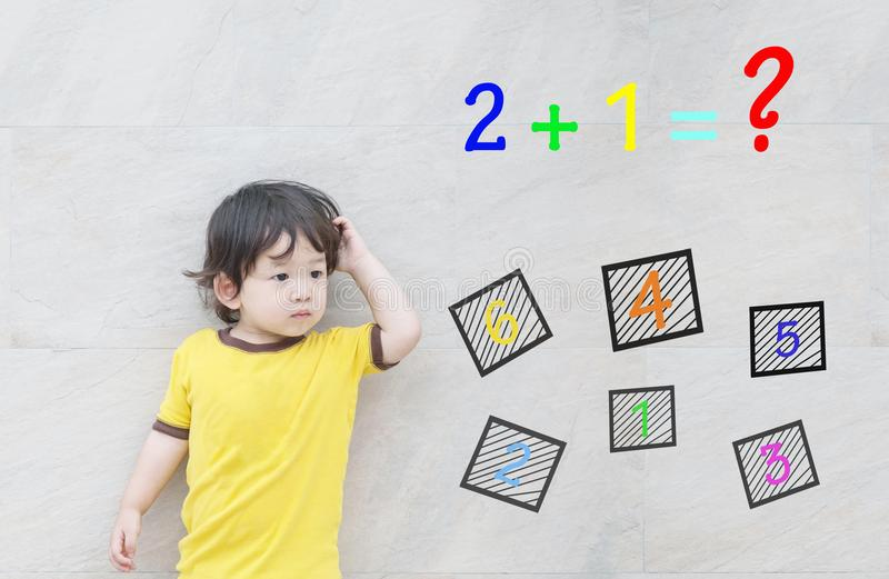 Closeup asian kid with confuse face by mathematic question on marble stone wall textured background. Closeup kid with confuse face by mathematic question on stock photography