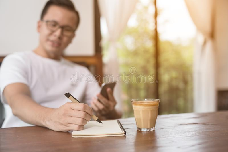 closeup asian male hand is writing a note in a cafe,Choose a focal point at the hands of men stock photos