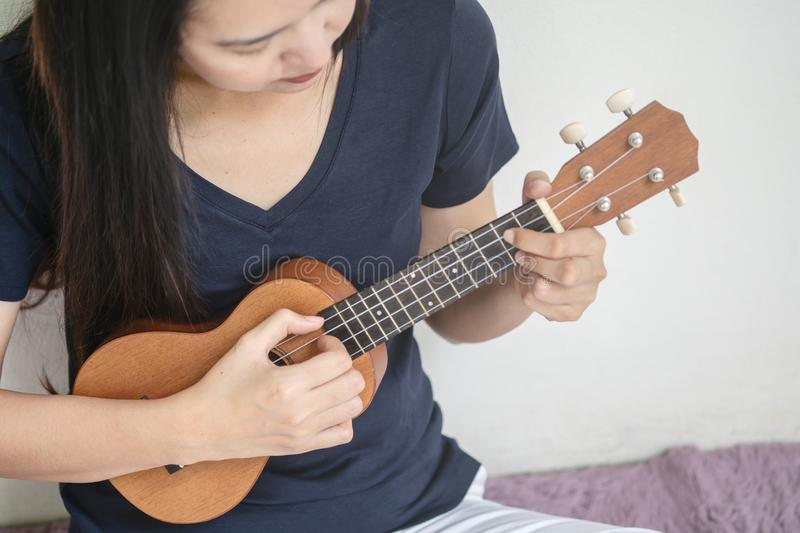 Closeup asian woman playing ukulele on white cement wall texture background with copy space stock photos